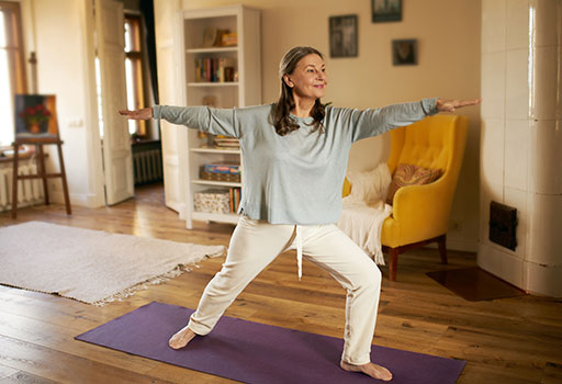 a woman does yoga as part of her parkinson's physical therapy program
